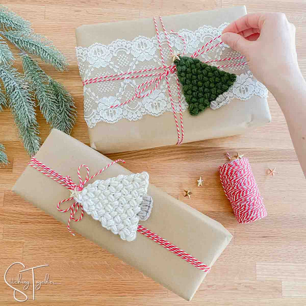 wrapped christmas presents with crochet trees and twine around them