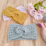 twisted crochet ear warmers, flowers, a hand holding a crochet hook and yarn
