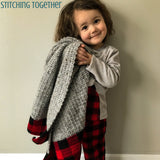 girl hugging a crochet baby blanket with buffalo plaid borders