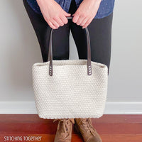 woman holding crochet bag with leather straps