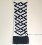 black and white crochet wall hanging with black fringe