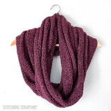 large crochet infinity scarf draped on a hanger