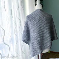 back of a gray crochet shawl on a mannequin