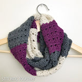 looped crocheted infinity scarf with stripes on a hanger