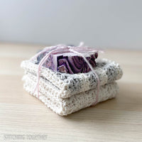 two crochet dishcloths folded and stacked with a bar of soap on the top