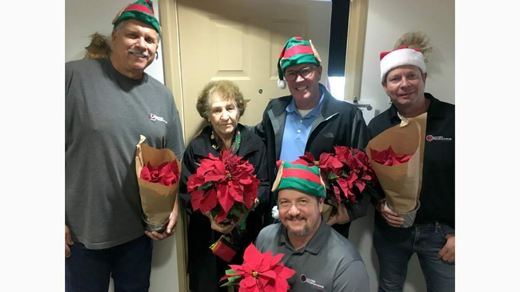 Jamboree and URSG hand out poinsettias to seniors at Heritage Villas in Mission Viejo.