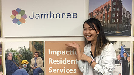 Affordable housing intern stands in front of Jamboree's Mission, Vision, Values artwork