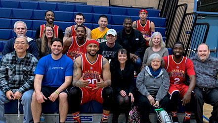 Jamboree residents pose with the Harlem Wizards at a basketball game.