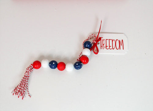 Red, white and blue wood bead garland with tassel and tag, which features the word freedom