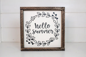 "Framed sign featuring the words, ""Hello summer,"" surrounded by leafy accents. Frame is stained in an espresso finish. Sign is painted cream with black lettering and accents"