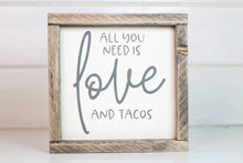 "Load image into Gallery viewer, Wood framed sign featuring the saying, ""All you need is love and tacos."" Frame is stained in Classic Gray finish. Sign is cream with gray vinyl lettering"