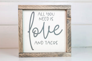 "Wood framed sign featuring the saying, ""All you need is love and tacos."" Frame is stained in Classic Gray finish. Sign is cream with gray vinyl lettering"