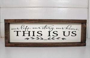 "Wood framed sign with the saying, ""Our life, our story our home. This is us."" Frame is stained with an espresso finish around a cream background and black lettering and accents"