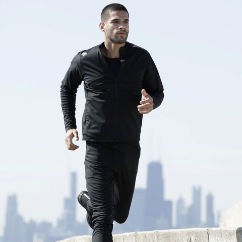 "{""alt"":""Triple Tech Utility Jacket being worn with the matching pants on model as he runs throughout the city""}"