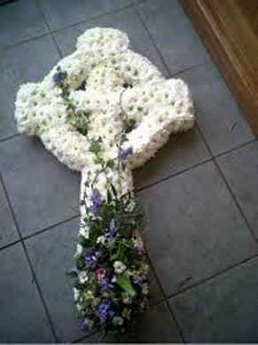 <p>A Traditional Celtic Cross makes this stunning Floral Tribuate. Created using a mass of white double chrysanthemums the finishing colours can be done in colour or style to suit the individual. Please contact us for further details.</p>