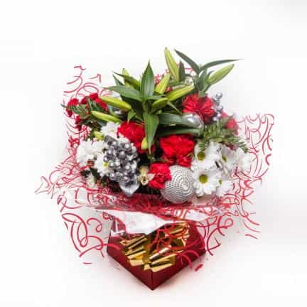 <p>Beautiful large headed oriental lillies make a very fitting centrepiece for this stunning Christmas Bouquet. Hand tied with a blend of mixed fresh flowers in seasonial reds, whites and silver to create a stunning Christmas Gift! </p><p>Contains Oriental Lillies, Chrysanthemums, Carnations, Hypericum and tropical foliage, wrapped in seasonal decoration and presented prefectly in a beautiful presentation box.</p><p> </p>
