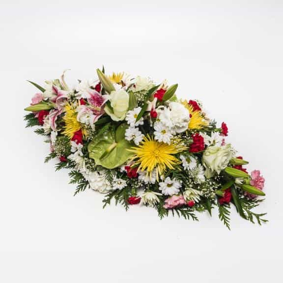 <p>A beautiful large colourful Arrangement to celebrate ones life.</p><p>Created using a range of fresh flowers including Lilies, Roses, Chrysanthemums and Carnations. Measuring approximately 75cm long (2.5 feet) this arrangement is ideally suited for a funeral remembrance. </p><p>If particular flowers or colours are required simple request them during the checkout stage.</p>