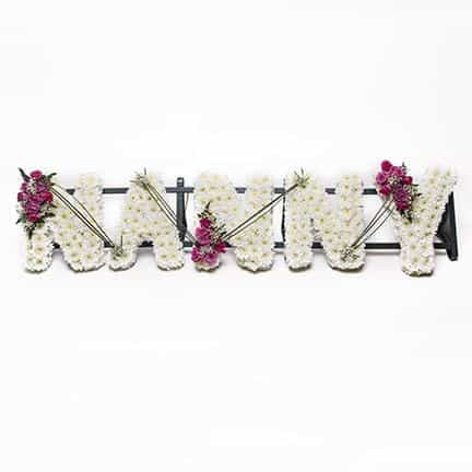 <p>A timeless piece ideal for a group of grand children to remember a loving Nanny.</p><p>Each letter is approximately 30cm high and 15cm wide. Created here in a mass of white double chrysanthemums and detailed with beautiful pink roses.</p><p>If desired this tribute can be created in different colours or styles, simply contact us to discuss.</p>