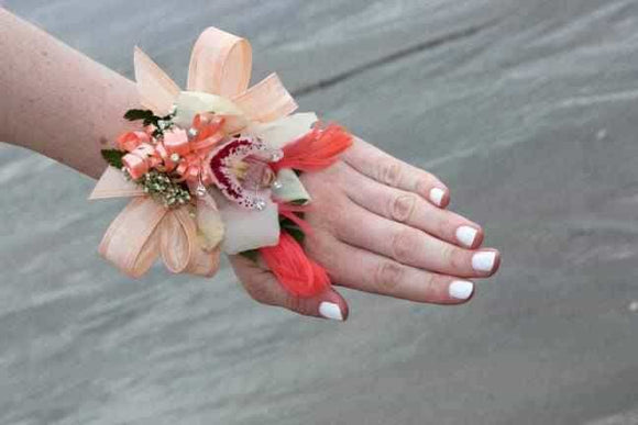 <p>A stunning White Cymbidium Orchid mounted on an orange background to create this striking corsage.</p><p>Providing glamour and drama the orchid is mounted on a beautiful pearl wristband.</p>