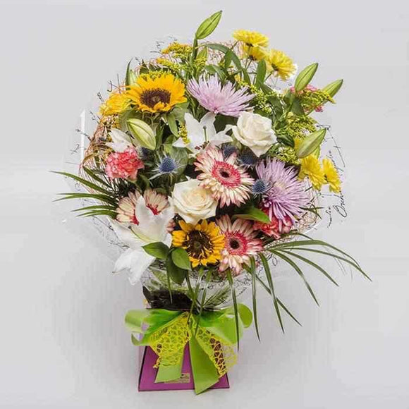 <p>A fantastic blend of fresh seasonial blooms artistically designed to show off each and every bloom at its best, guaranteed to light up everyone's day!</p><p>Designed in a modern style using an inbuild water reservoir allowing the flowers to be left in this arrangement.</p><p>Contains an Orchid, Oriental Lillies, Colourful Roses, Pretty Carnations and Chrysanthemum Blooms, expertly wrapped in seasonial wrapping and presented in a beautiful presentation box.</p>
