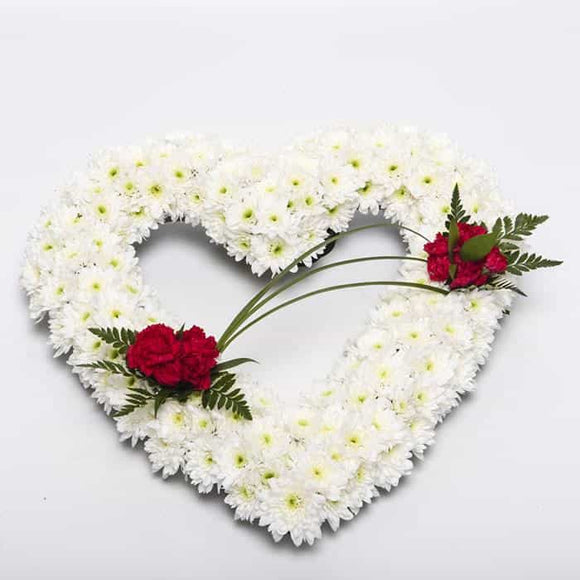 <p>A tribute to a love gone but not forgotten.</p><p>Finished here in a mass of white double chrysanthemums with red roses, this arrangement measures 45cm across (17