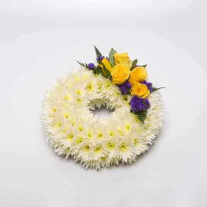 "<p>A Classic meaningful arrangement. Created on a 25cm ring (10"") and decorated using a mass of double headed chrysanthimums  and decorated with a touch of colour using roses.</p><p>In the examples shown yellow roses are used to decorate, simply contact us with your requirements if other colours are preferred.</p>"