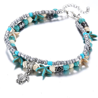 A boho beach anklet with turqoiuse starfish and a jeweled turtle charm.