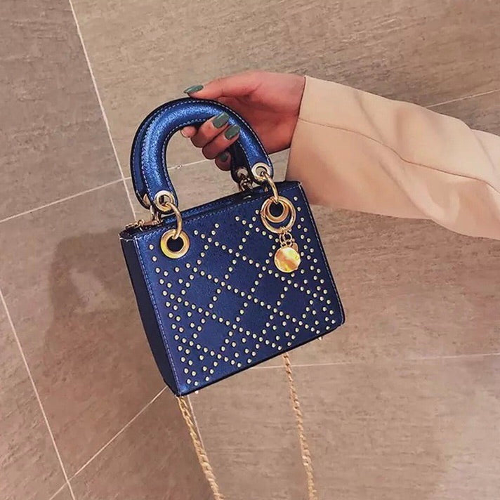 Women's blue and gold metallic studded handbag with top handle