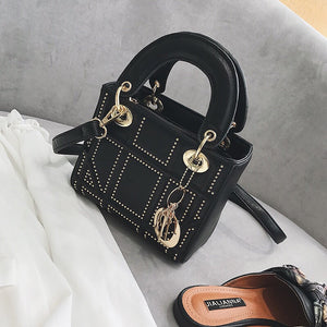 Ladies black handbag with gold studded detail and detachable charm
