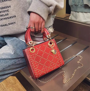 Women's red and gold metallic studded handbag with top handle
