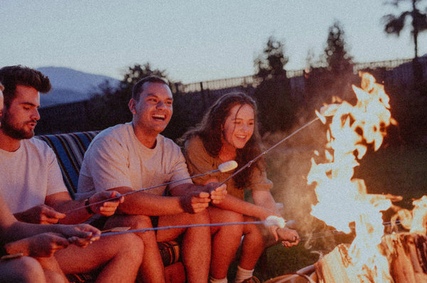 11 Out of the Ordinary Hangout Ideas. Friends smile as they gather around the campfire.