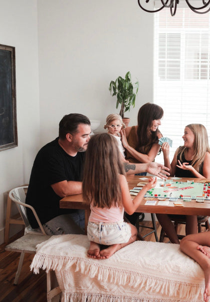 29 Fun Activities To Do At Home With The Kids. Family playing board games in their living room.