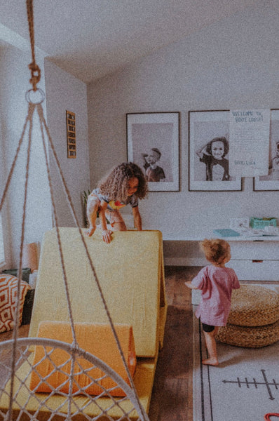 29 Fun Activities To Do At Home With The Kids. Two little girls building a fort in their living room.