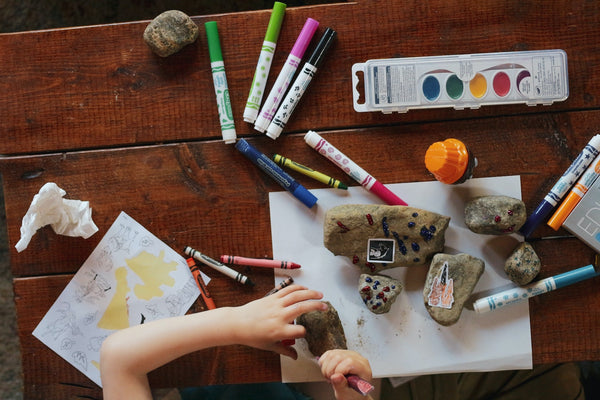 29 Fun Activities To Do At Home With The Kids. Kid painting rocks with coloring materials strewn across her desk.