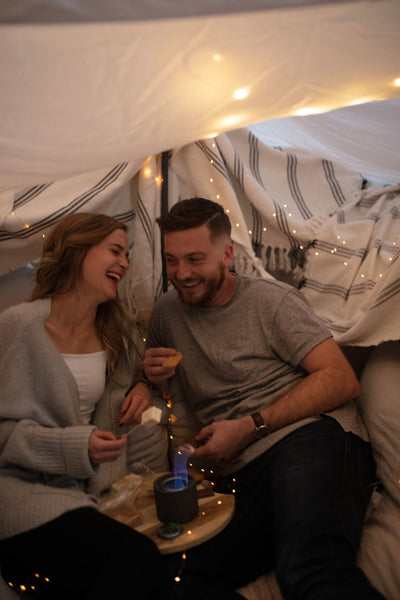 Cheap Date Ideas (That Don't Feel Cheap). Couple share laughs as they roast marshmallows in the fort that they built and decorated with fairy lights.
