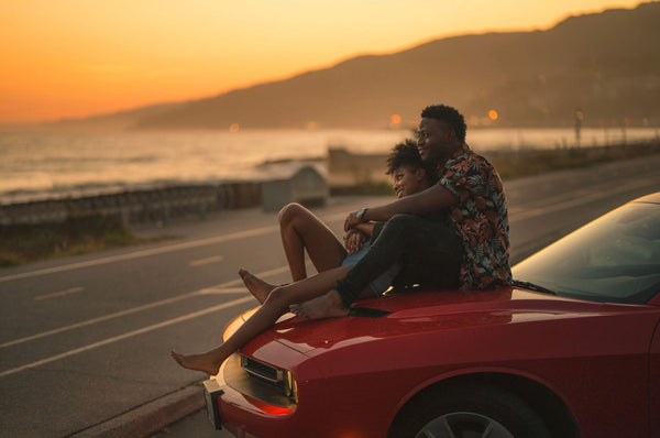Cheap Date Ideas (That Don't Feel Cheap). Couple smile as they watch the sunrise on the hood of their car.