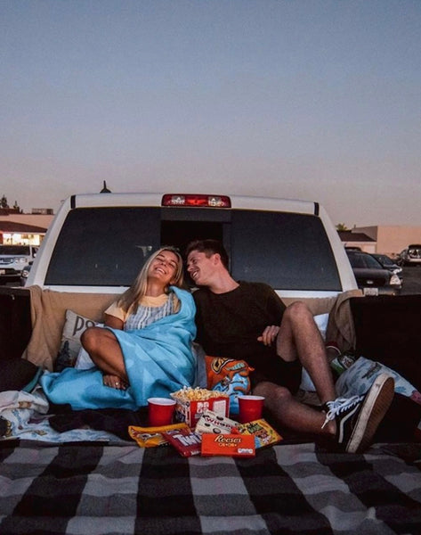 Cheap Date Ideas (That Don't Feel Cheap). Couple snuggle at the back of their pick-up truck with some snacks as they enjoy a drive-in movie.
