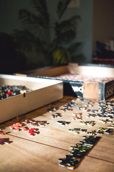 Cheap Date Ideas (That Don't Feel Cheap). Close-up photo of scattered puzzle pieces on a wooden table.
