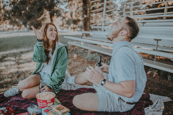 Cheap Date Ideas (That Don't Feel Cheap). Couple having an outdoor picnic together, with the girl feeding the guy popcorn.