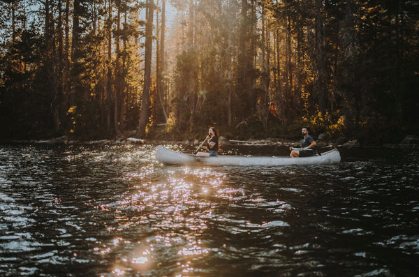 Adventure Date Ideas Will Turn the Heat Up. Couple being active and canoeing in  a pristine lake.