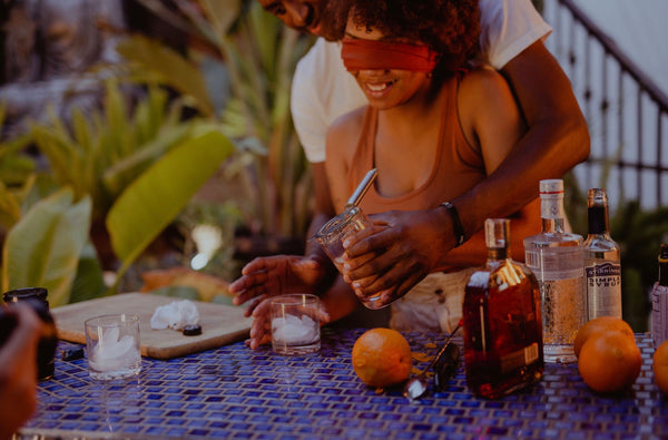 Adventure Date Ideas Keep You Present and Connected. Couple making drinks, with the girlfriend blindfolded and the boyfriend guiding.
