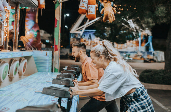 Adventure Date Ideas Will Show You New Sides of One Another. Couple smiling as they play a game at the fair.