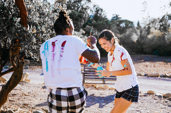 Adventure Date Ideas Reignite the Romance. Couple laughing and having fun as they playfully splash paint at each other.