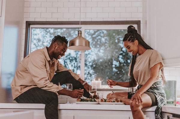Couple sit on a kitchen counter and have themselves an intimate at-home dinner date
