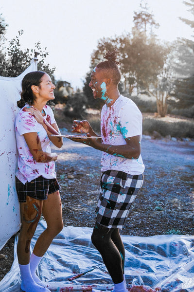 How to Bring Intimacy Back Into a Relationship. Couple laugh as they splatter paint all over each other.