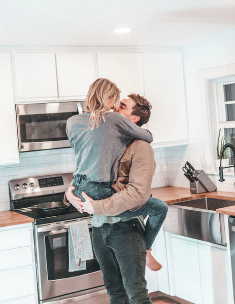 How to Have Better Sex In a Relationship. Guy holding girl in the kitchen as they are about to share a kiss.