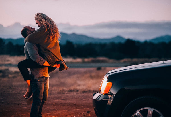 How to Increase Intimacy in a Relationship. Guy carries girl as they look into each other's eyes in the middle of a picturesque grassland.