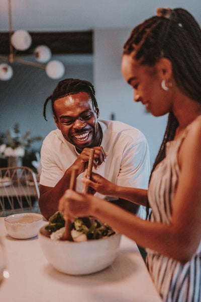 How to Spice Things Up in The Bedroom in 2021. Couple laughing as they chat casually int the kitchen as the girl prepares a meal on the counter.