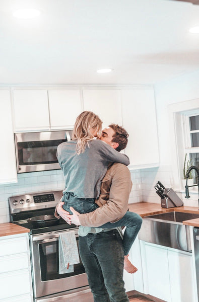 How to Spice Things Up in The Bedroom in 2021. Boyfriend carries girlfriend in his arms as they stand in the middle of the kitchen.