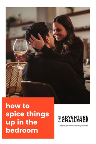 Girlfriend sitting on boyfriend's lap while facing him and holding a wine glass in her free hands; image overlaid with text that reads How to Spice Things Up in The Bedroom